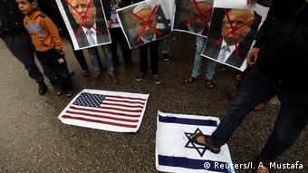 Protesters stand on American and Israeli flags, holding pictures of Donald Trump's face crossed out with red.
