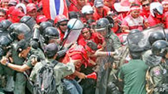 Police wearing safety gear tackle red shirted protesters