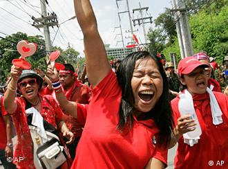 A woman in a red shirt raises her arm