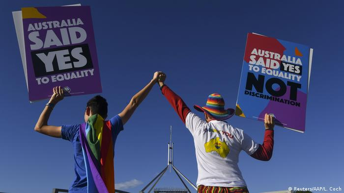 Two people hold up signs in favor of same-sex marriage. (Reuters/AAP/L. Coch)