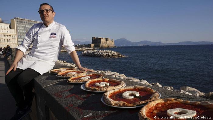 Gino Sorbillo, Pizzabäcker aus Neapel, sitzt auf einer Mauer, darauf sechs Pizzen, die jeweils einen Buchstaben aus Mozzarella zeigen, die zusammen das Wort UNESCO ergeben (picture alliance/ANSA/dpa/C. Abbate)