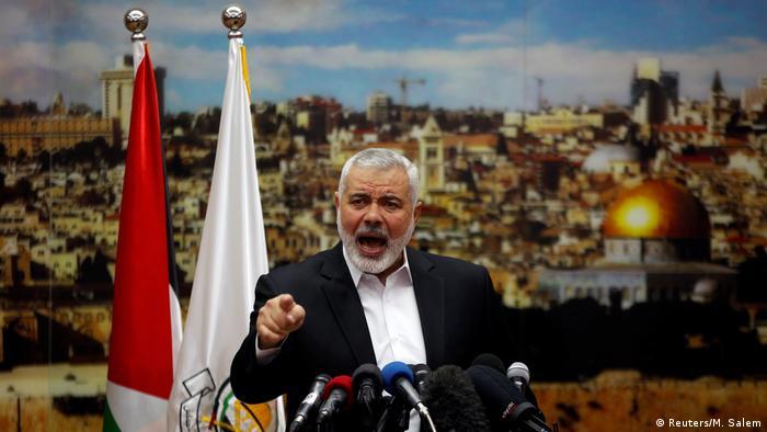Hamas leader Ismail Haniyeh speaks to a crowd, standing behind microphones.