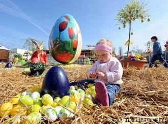 A small child sitting in hay, looking over some eggs