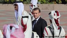French President Emmanuel Macron (R) and Qatari Emir Sheikh Tamim bin Hamad al-Thani review the honour guard during a welcome ceremony in the Qatari capital Doha on December 7, 2017. / AFP PHOTO / KARIM JAAFAR