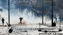 7.12.2017**** Palestinian protesters run for cover from tear gas fired by Israeli troops during clashes at a protest against U.S. President Donald Trump's decision to recognize Jerusalem as the capital of Israel, in the West Bank city of Bethlehem December 7, 2017. REUTERS/Mussa Qawasma