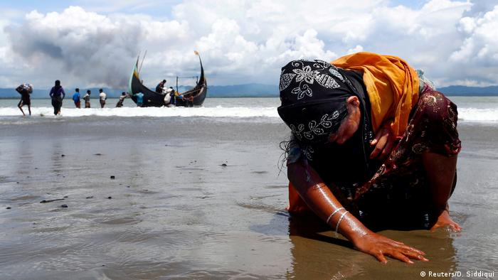 An exhausted Rohingya refugee woman touches the shore after crossing the Bangladesh-Myanmar border