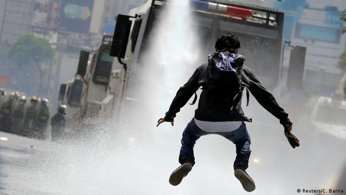 A demonstrator jumps away from a jet of water released from a security vehicle during a rally against Venezuelan President Nicolas Maduro in Caracas. (Reuters/C. Barria)