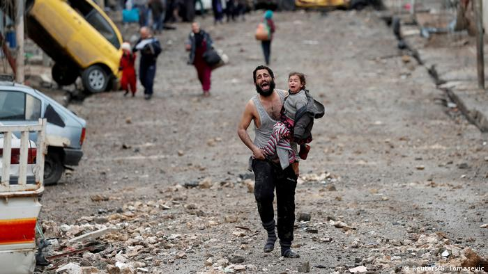 Man holding his daughter as he runs down a street in Mosul (Reuters/G. Tomasevic)