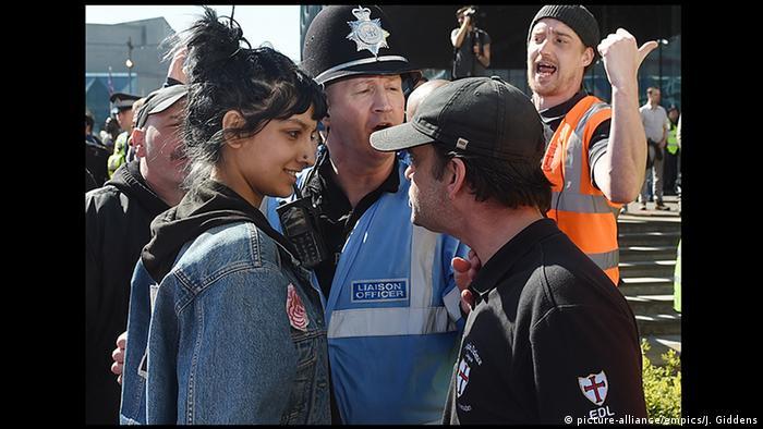 صفیه خان (چپ)، فعال مدنی در بریتانیا با چهرهای آرام و با لبخند با رهبر گروه راستگرای افراطی لیگ دفاع از انگلیس روبرو شد و به نماد شهامت مدنی علیه راستگرایان بدل گردید. او در یک تظاهرات در بیرمنگام به کمک یک زن باحجاب که مورد تهدید تظاهرکنندگان راستگرا قرار داشت، شتافته بود. لیگ دفاع از انگلیس جزیی از موج گرایشهای راستگرایانه و ضداسلامی در اروپا است.