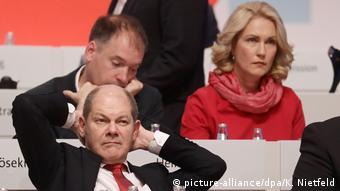 Олаф Шольц сидит, закинув руки за голову, на съезде социал-демократов в 2017 году