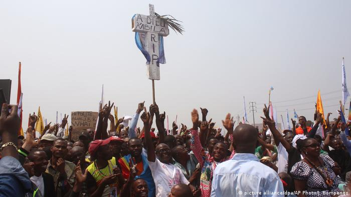 Protesters hold up a cross that reads A Dieu Kabila (photo: picture alliance/dpa/AP Photo/J. Bompengo)