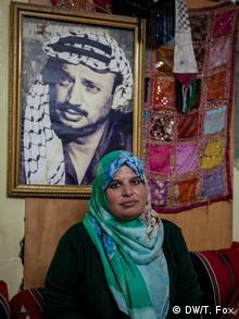 A woman sitting under a portrait of Yasser Arafat