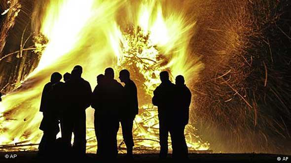 Fires burn with human silhouettes in front of them (AP Photo/Frank Drechsler)