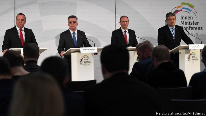 Four interior ministers standing at desks in Leipzig (picture-alliance/dpa/H. Schmidt)