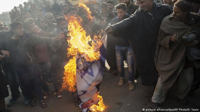 Muslim men burn Israeli and US flags during a protest in Budgam, southwest of Srinagar, in Indian-controlled Kashmir. Protesters marched in several places in Srinagar and other parts of the region after Friday prayers chanting slogans such as Down with America and Down with Israel. (picture alliance/dpa/AP Photo/D. Yasin)