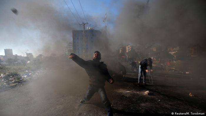 A Palestinian protester hurls stones toward Israeli police during clashes as Palestinians call for a day of rage in response to US President Donald Trump's decision to recognize Jerusalem as Israel's capital, near the Jewish settlement of Beit Al, near the West Bank city of Ramallah. (Reuters/M. Torokman)