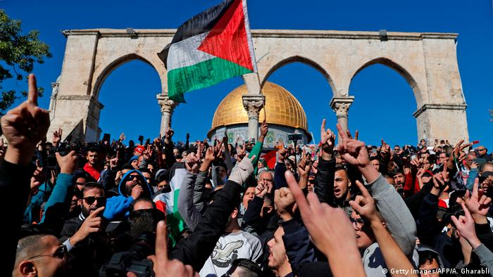 Palestinian protesters shout slogans in front of the Dome of the Rock mosque at the al-Aqsa mosque compound in Jerusalem's Old City. Hundreds of additional police were deployed to control the masses of protestors after Palestinian calls for protests following the Friday prayers. (Getty Images/AFP/A. Gharabli)