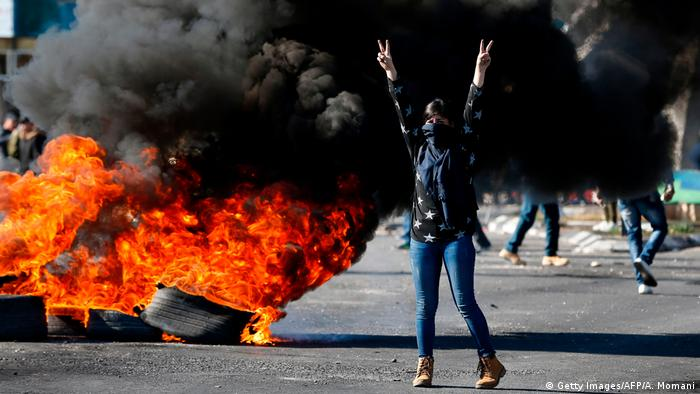 A protester standing in front of burning tires in Ramallah