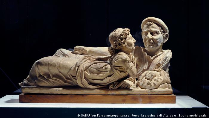 An urn lid made of a light stone showing an older, lying couple. (Foto: Uli Deck)