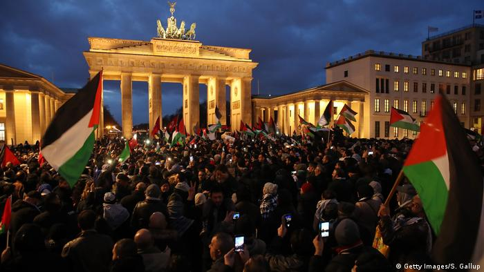 People waving Palestinian and Turkish flags gather in front of the Brandenburg Gate to protest against U.S. President Donald Trump's announcement to recognize Jerusalem