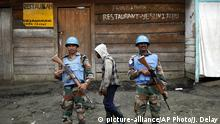 FILE - In this Friday Nov. 30, 2012 file photo, Two UN soldiers stand guard in Goma, Democratic Republic of Congo. Rebels attacked a United Nations peacekeeping base in eastern Congo, killing at least 14 peacekeepers and wounding 40 others Friday Dec. 8 2017, in the worst violence against the mission in this Central African country in years. Deputy spokesman Farhan Haq in New York said the peacekeepers were mainly from Tanzania, and that at least five Congolese soldiers also were killed in the assault blamed on one of the region's deadliest rebel groups. (AP Photo/Jerome Delay File) |