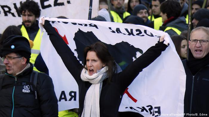 A woman holds a banner over her head