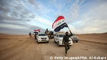 Irakischer Kämpfer mit Nationalflagge (Getty Images/AFP/A. Al-Rubaye)