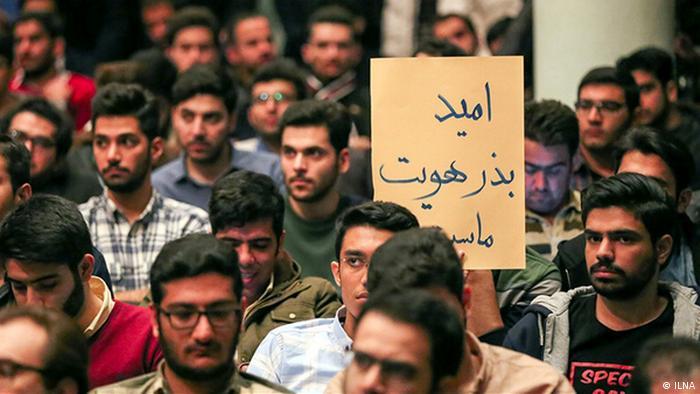 دانشجویی در جمع دانشجویان دیگر با پلاکاردی کوچک که بر آن نوشته شده امید بذر هویت ماست