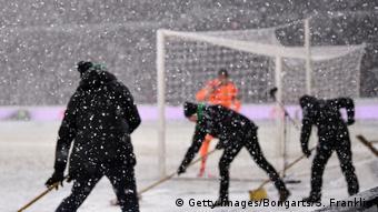 Voluntários limpam campo de futebol cheio de neve