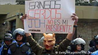 An opposition supporter holds up a sign at a demontration in front of the US Embassy in Tegulcigalpa on December 10. (Getty images/AFP/O. Sierra)