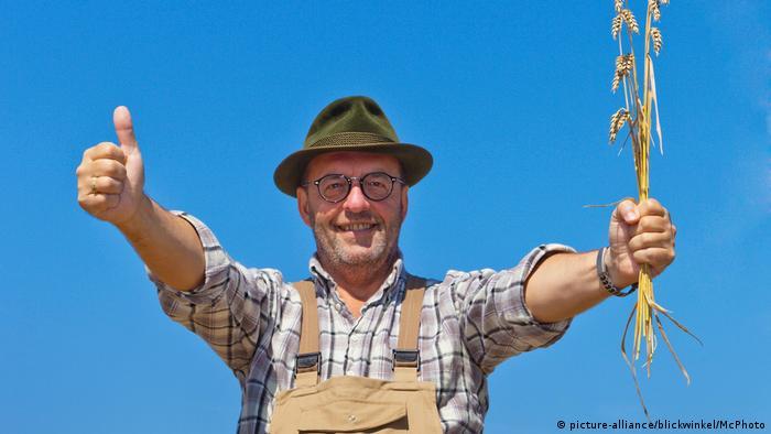 Ein Bauer hält eine Weizenähre hoch und reckt den Daumen der linken Hand zum Zeichen einer guten Ernte in die Luft.