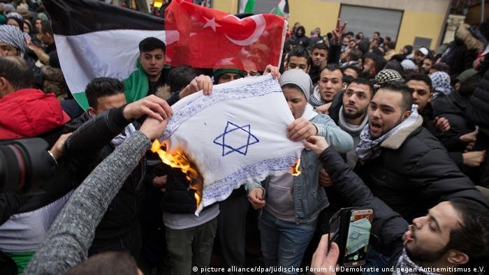 Protestors burn a makeshift Israeli flag in Berlin