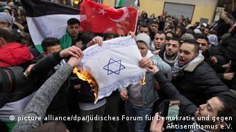 Pro-Palestinian demonstrators at a rally in Berlin burn a Jewish prayer shawl emblazoned with a Star of David (picture alliance/dpa/Jüdisches Forum für Demokratie und gegen Antisemitismus e.V.)