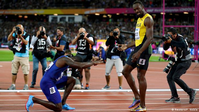 Justin Gatlin kneels down in front Usain Bolt (Reuters/P. Noble)