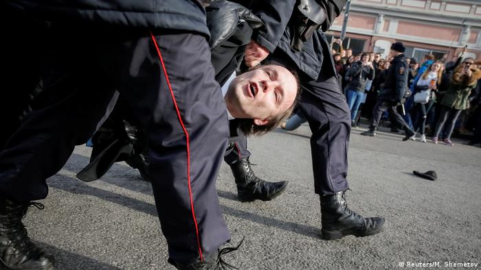 Man being manhandled by police (Reuters/M. Shemetov)