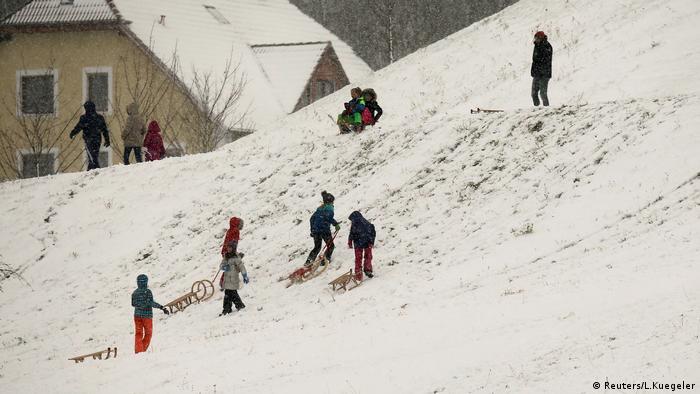 Crianças brincam com trenós de neve.