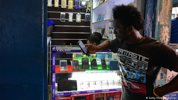 A man in a t-shirt with the word fantastic looks at his smartphone at the counter of a smartphone vendor in Abidjan, Ivory Coast (Getty Images/I.Sanogo)