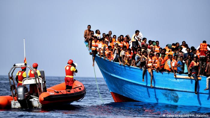 Rescuers try to aid migrants packed onto a boat bound for the EU.