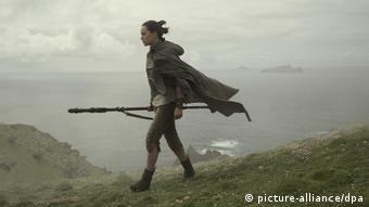 A woman walks along the edge of a cliff in a still from Star Wars: The Last Jedi