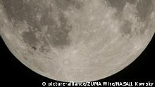 The International Space Station, with a crew of six onboard, is seen in silhouette as it transits the Moon (picture-alliance/ZUMA Wire/NASA/J. Kowsky)