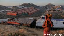 A Rohingya refugee child stands on a hill above the camp