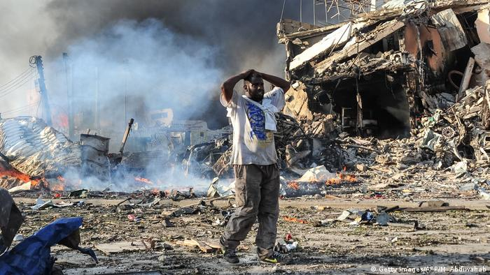 A man holding his hands over his head at the site of a bomb blast