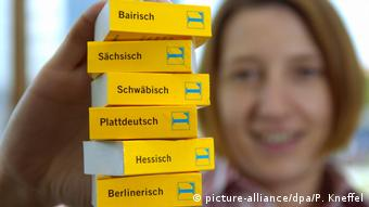 A girl holds up a stack of dictionaries titled with the names of various German dialects