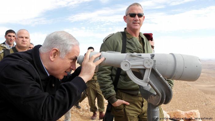 Netanjahu looks through binoculars at Israel's border