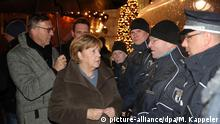 Merkel meets with police at the Breitscheidplatz Christmas market just days before the anniversary of last year's terror attack (picture-alliance/dpa/M. Kappeler)