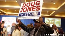 Voter holding up Doug Jones sign during Alabama election night
