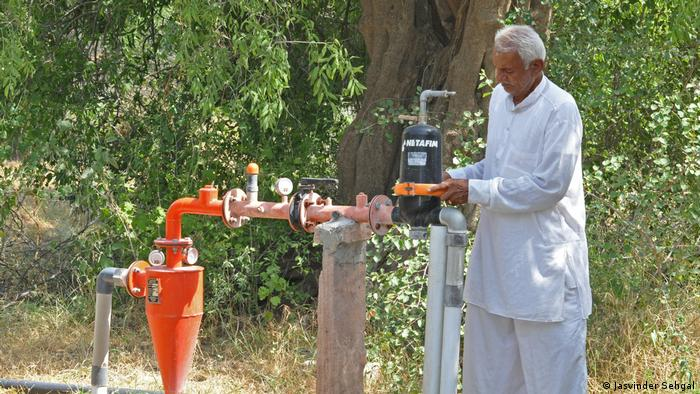 A man standing by a water pump
