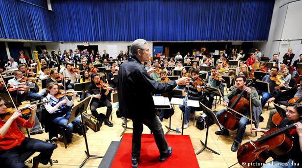 Conductor Michael Tilson Thomas (c), leading the 2009 YouTube Symphony Orchestra at a rehearsal in New York City