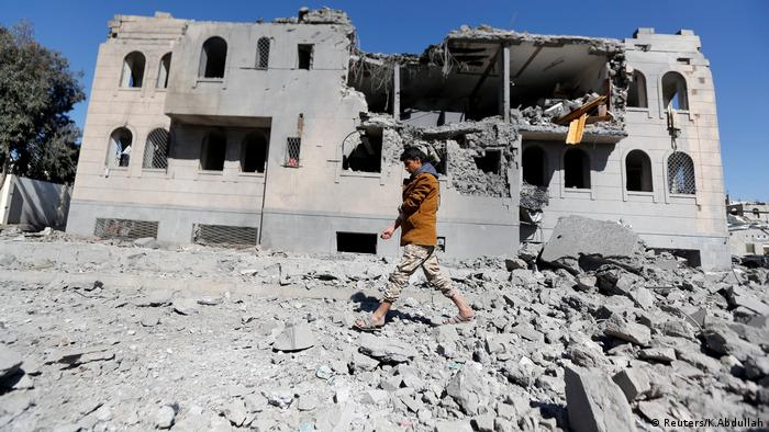 صنعا؛ یک حوثی مسلح از برابر زندانی بمباران شده می گذرد