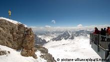 Besucher der Zugspitze genießen am 30.04.2012 die Aussicht auf die Berge und das Gipfelkreuz. Mit knapp 3000 Metern Höhe ist die Zugspitze der höchste Berg Deutschlands. Foto: Sven Hoppe dpa/lby | Verwendung weltweit